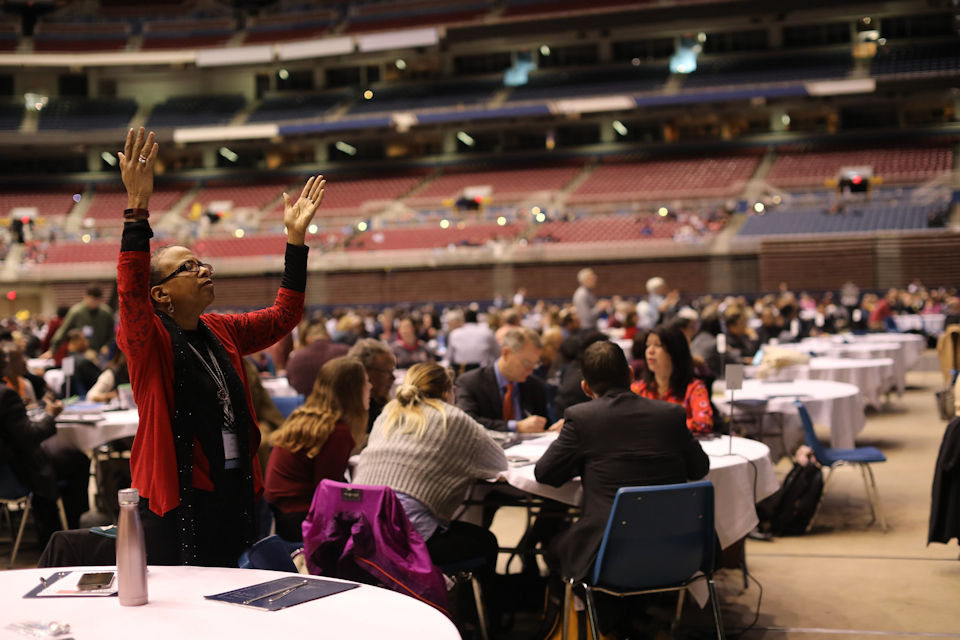 Woman praying at St. Louis General Conference.