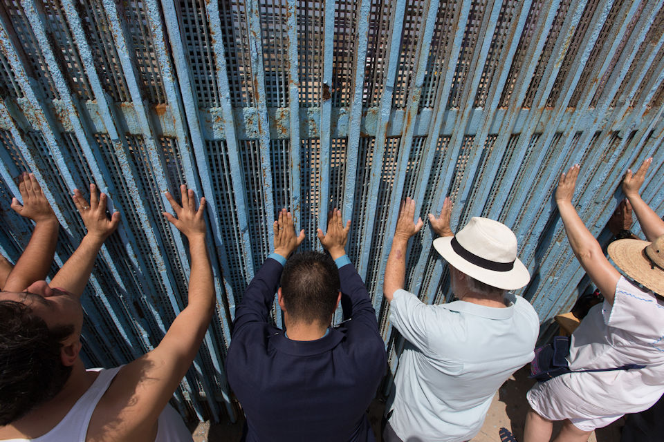 People celebrate communion at border fence