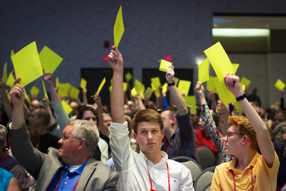 Conference members hold cards in the air to vote at the Michigan Annual Conference.