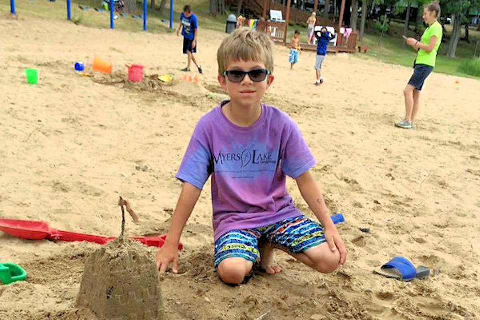 Boy playing in sand at Myers Lake camp site