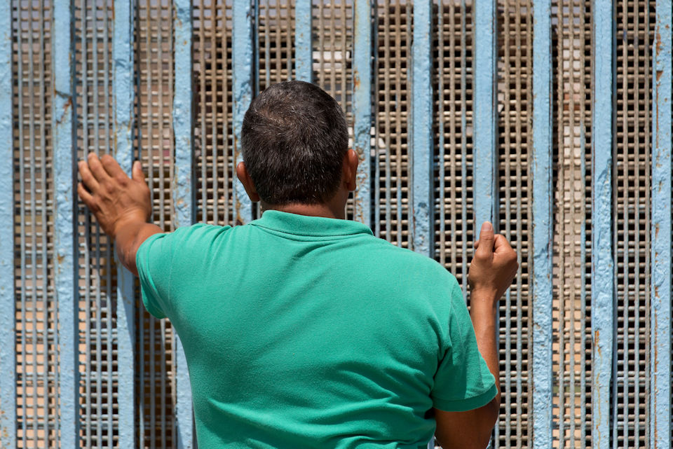 Man standing at the wall in Tijuana, Mexico.