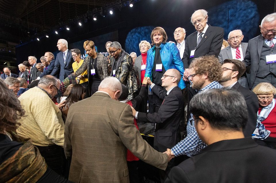 Delegates and Bishops pray together during 2019 General Conference.