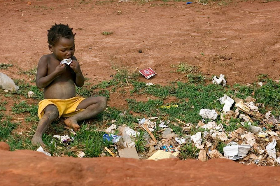 Child suffering from hunger eating at garbage pile
