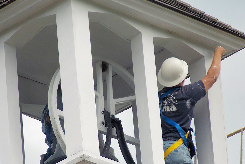 Man works on belfry of historic church.