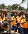 Children in Liberia gather around pump
