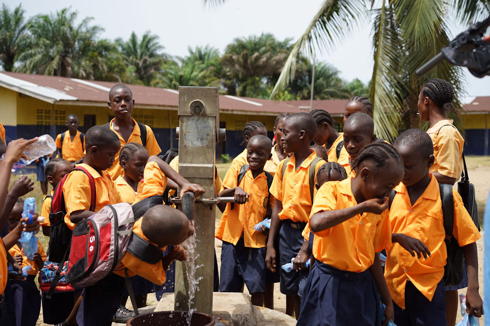 Children in Liberia gather around pump