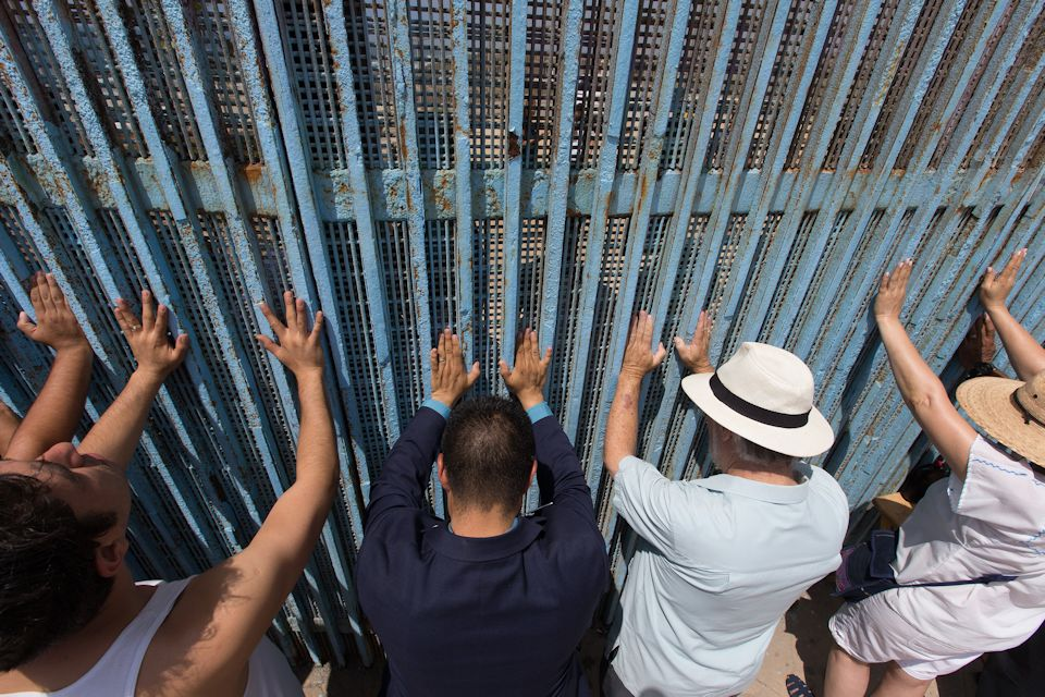 Latinos are separated physically and spiritually by the border wall between Mexico and US.