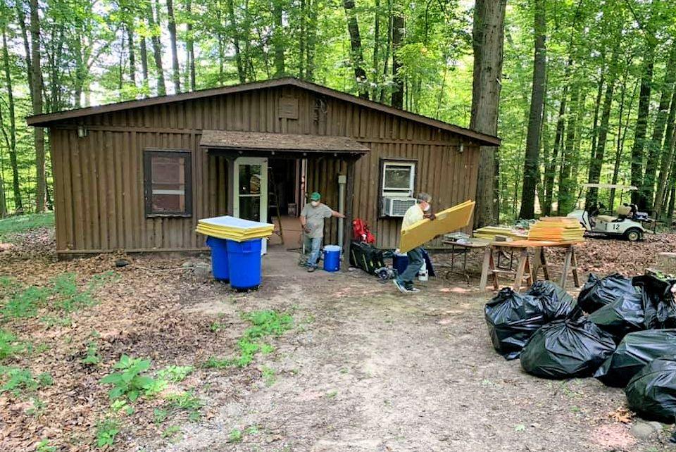 Volunteers clean a cabin