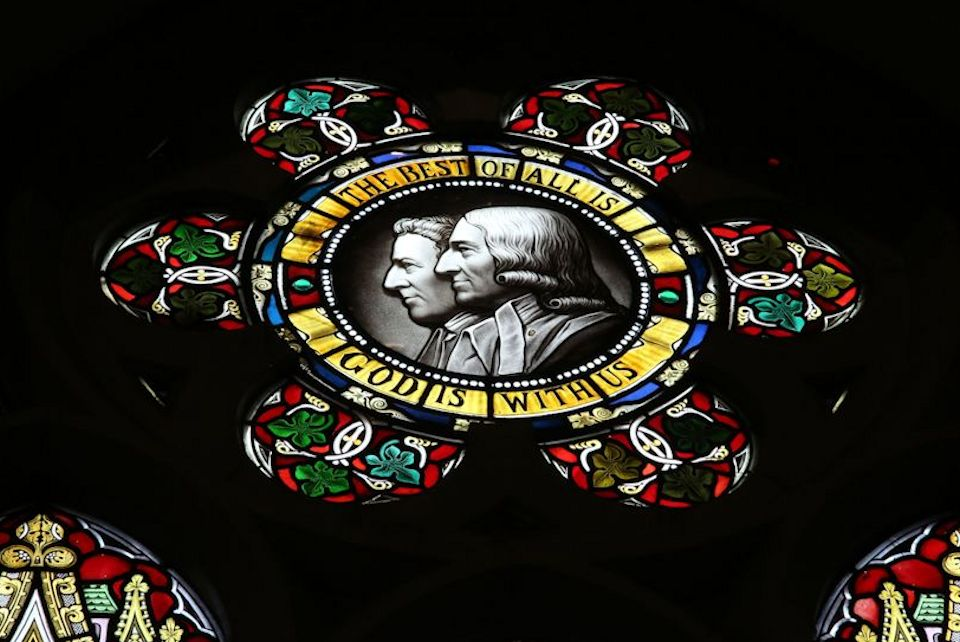 Stained glass with Wesleys and statement of grace.